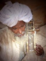 Indian folk musician in white turban in Rajasthan plays the kamayacha